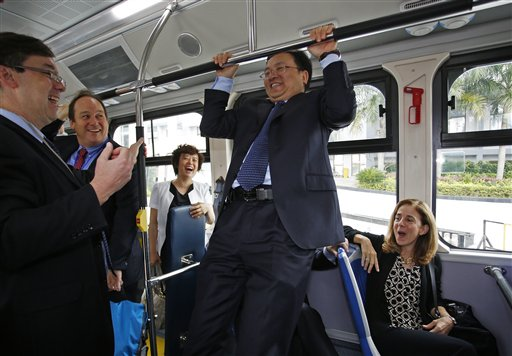 Wang Chuanfu, founder and chairman of Chinese automaker BYD Co., center, does a chin-up in an electric bus during a visit by California Gov. Jerry Brown at the headquarters in Shenzhen, China, on April 16, 2013.
