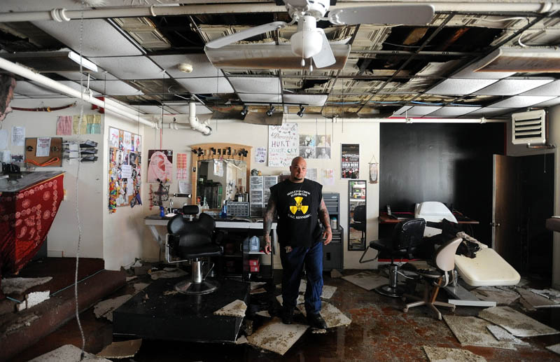 Bill Juliano, 38, owner of Ink-4-Life, located on the first floor of the Main Street building gutted by fire Friday, sifts through his tattoo equipment Saturday morning.