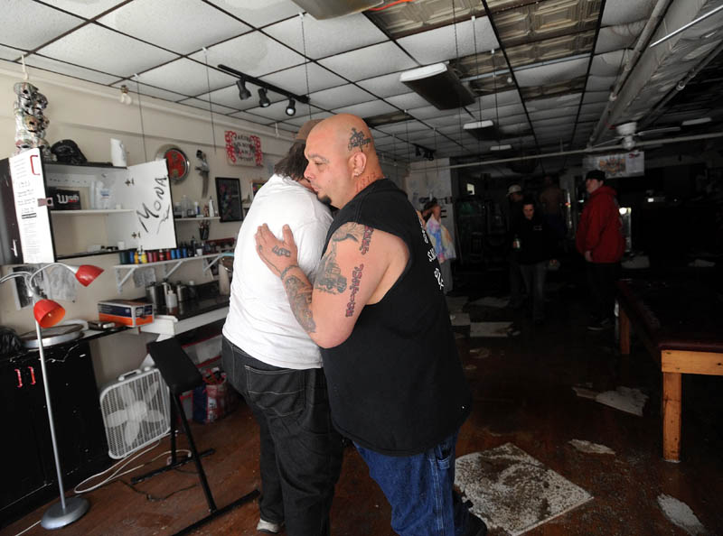Bill Juliano, right, receives a hug from friend Shane Lake, in the Ink-4-Life on Main Street in downtown Waterville Saturday morning. The tattoo studio, along with three floors of apartments above, were destroyed Friday by fire.