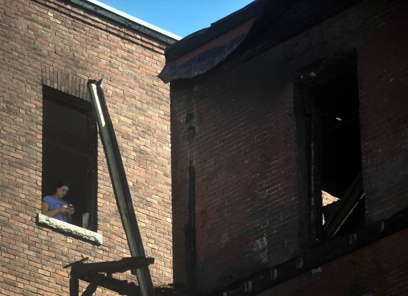 A woman is seen Saturday in the window of a Main Street, Waterville building that was damaged by fire Friday,