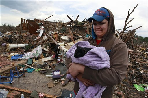 Austin Brock holds cat Tutti, shortly after the animal was retrieved from the rubble of Brock's home, which was demolished by Monday's tornado.
