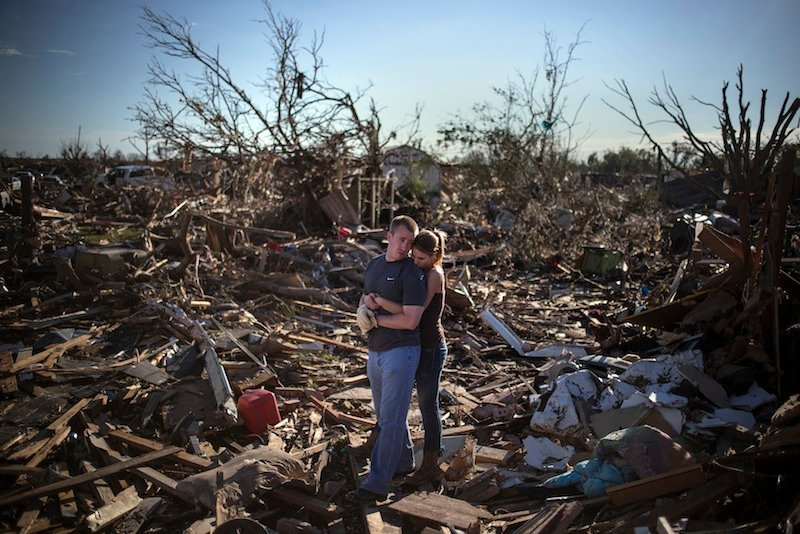 Danielle Stephan holds boyfriend Thomas Layton as they pause between salvaging through the remains of a family member's home one day after a tornado devastated the town Moore, Oklahoma, in the outskirts of Oklahoma City May 21, 2013. Rescuers went building to building in search of victims and thousands of survivors were homeless on Tuesday after a massive tornado tore through the Oklahoma City suburb of Moore, wiping out whole blocks of homes and killing at least 24 people. (REUTERS/Adrees Latif) :rel:d:bm:GF2E95M00JG01