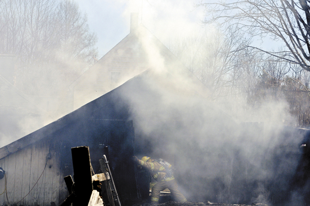 A firefighter pops open the door to a barn that burned Wednesday with a garage attached to a home in Readfield. Firefighters from several communities were able to contain the blaze from heavily damaging the home, according to Wayne Deputy Fire Chief Brian Roche.