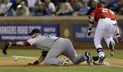 Boston Red Sox first baseman Mike Napoli (12) can't handle the throw at first base, allowing a two-run RBI single, by Texas Rangers Craig Gentry (23) during the fourth inning of a baseball game Saturday, May 4, 2013, in Arlington, Texas. Rangers Adrian Beltre and A. J. Pierzynski scored on the play.(AP Photo/LM Otero)
