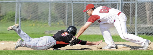 YOU'RE OUT: Skowhegan's Kaleb Brown, left, can't beat the pick-off throw back to first base in time and gets tagged out by Cony's Ben Lucas on Friday in Augusta.