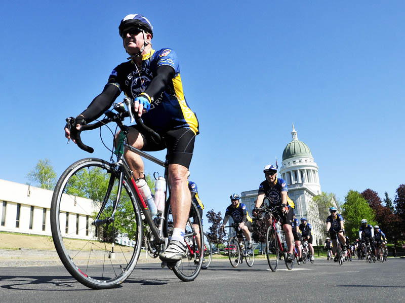 Bicyclists for the National EMS Memorial bike ride roll into the Maine EMS memorial event on Saturday near the State House in Augusta.
