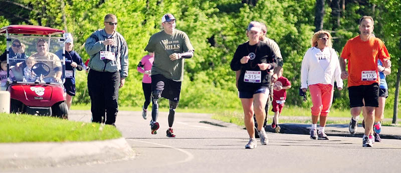 Staff Sgt. Travis Mills, center, talks to passing runners as he walks part of the course at the second annual Miles For Mills 5k on Monday at Cony High School in Augusta.