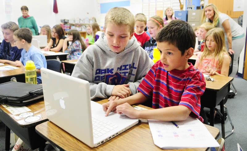 Oak Hill Middle School seventh-grader Eric O'Connor, left, works with Carrie Ricker School third-grader on a MacBook on May 14 in Litchfield. Gov. Paul LePage sought to eliminate Maine's middle-school laptop program, according to emails received by MaineToday Media, but was persuaded against that move by Education Commissioner Stephen Bowen.
