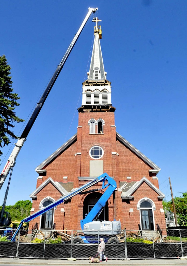 A pedestrian walks past the St. Francis de Sales Catholic Church in Waterville as the cross and steeple are being removed on Tuesday. The church is being torn down and a housing complex will be built at the location.