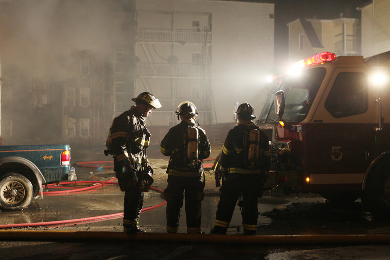Firefighters confer at the scene of a Lewiston fire that destroyed 29 aparments early Saturday.