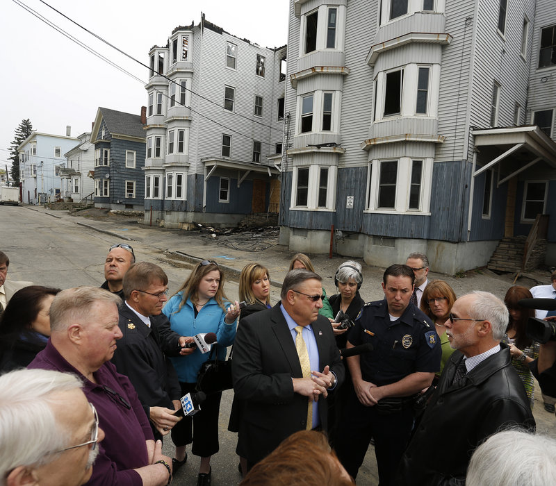 "Gov. Paul LePage talks to the media Tuesday while meeting with Lewiston officials in front of two buildings that burned Monday on Bartlett Street. Asked if he was happy to be back in his hometown, where he was homeless as a youth for two years, he said, ""It brings back a lot of bad memories."""