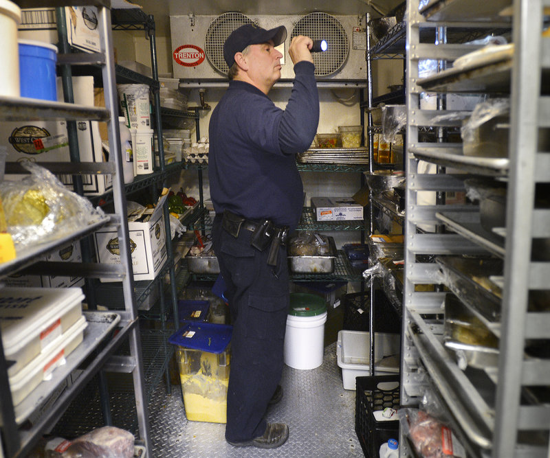 Scott Davis, a state health inspector, checks a walk-in cooler at the Stage Neck Inn in York Harbor. The Legislature scaled back the frequency of restaurant inspections to once every two years, making Maine's rule among the most lax in the nation. Many other states require multiple inspections each year.