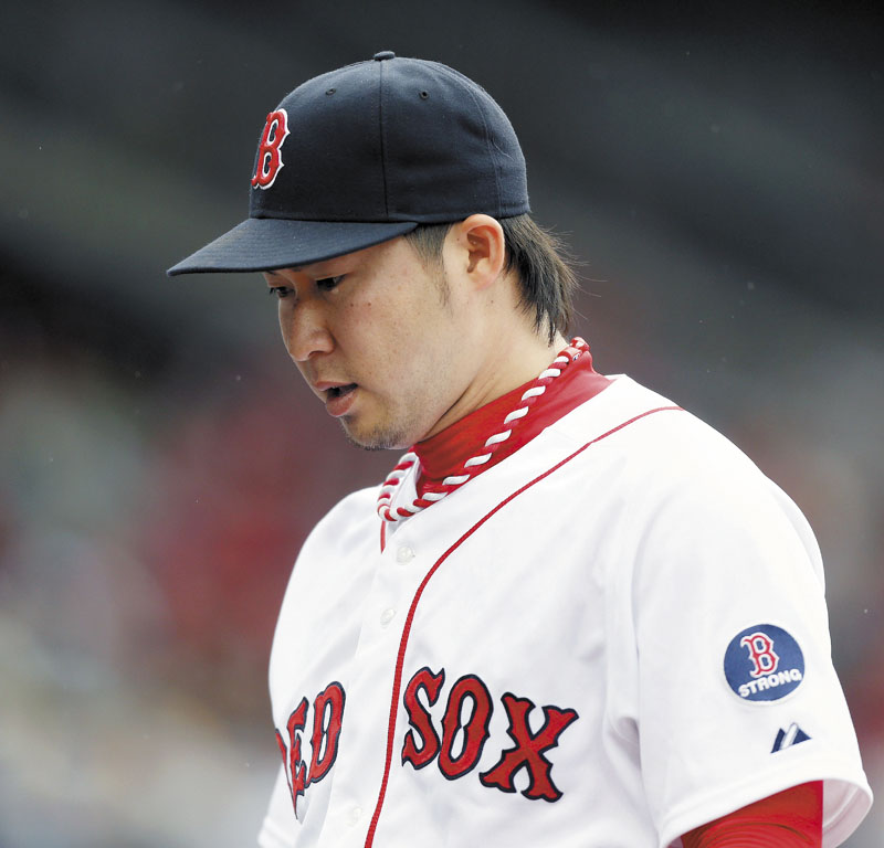 TOUGH DAY: Boston's Junichi Tazawa walks off the field after the top of the ninth inning of the Red Sox' game against the Toronto Blue Jays on Saturday in Boston. Tazawa gave up a home run in the ninth and the Sox lost 3-2.