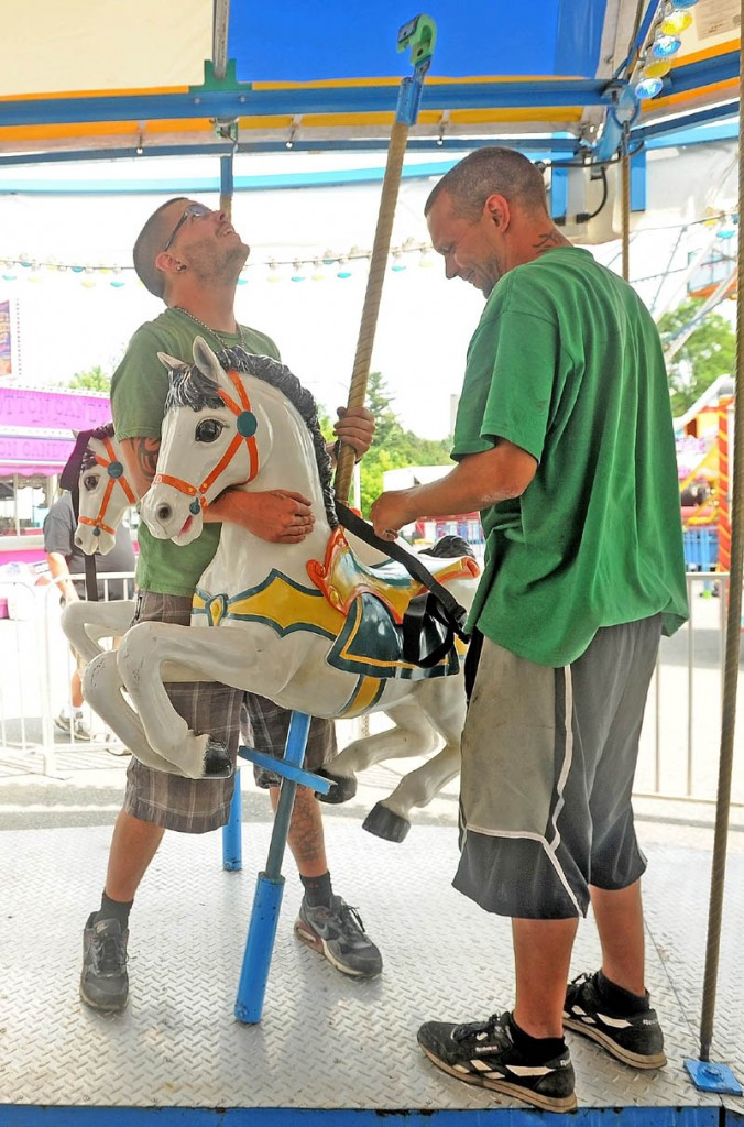 Adam Trott, 25, left, and Tim Siwek, 32, right, install a horse on the merry-go-round at the East Coast Midways carnival in Fairfield on Tuesday.