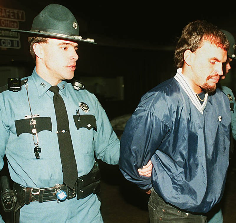 Trooper Joseph Mills II leads Guy E. Hunnewell III from the State Police Criminal Investigation Division in Augusta where he was detained after being arrested at the Comfort Inn in 1998. Hunnewell later pleaded guilty to murder.