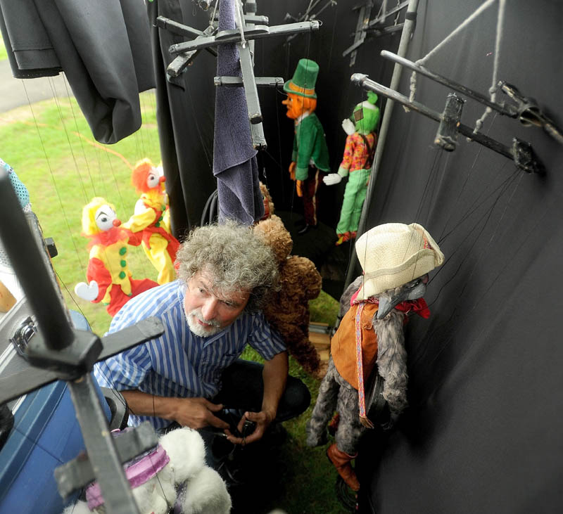 Puppeteer Dan Grady prepares his marionettes for a series of three shows at Meeting House Park, during the first Summer Solstice Celebration in downtown Farmington on Saturday.