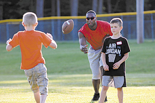 HERE IT IS: Former New England Patriots player Eric Alexander tosses a football to 8-year-old Trent Worcester of Madison while running the annual Central Maine Football Clinic on Friday in Waterville. Looking on is Jayden Meader, 7, of New Sharon, right. The clinic will continue from 9 a.m. to 3 p.m. today at Rummel Field off West River Road.
