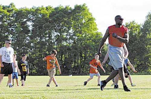 RUNNING THE DRILL: Former New England Patriots player Eric Alexander runs a conditioning drill at the annual Central Maine Football Clinic on Friday night in Waterville. The clinic will continue from 9 a.m. to 3 p.m. today at Rummel Field off West River Road.