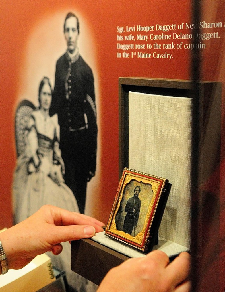 Conservation specialist Linda Carrell positions a photograph in a display case of an exhibit titled