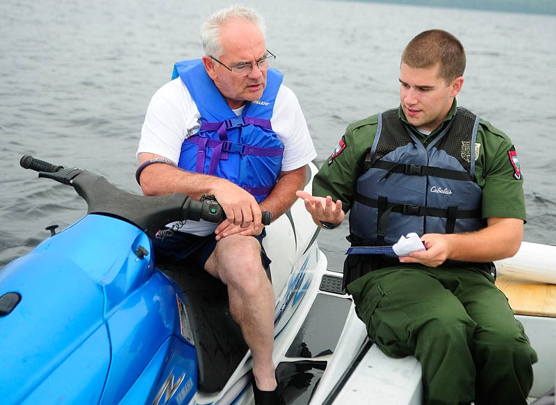 Deputy Game Warden Harry Wiegman, right, talks to Frank Card while doing a safety check.