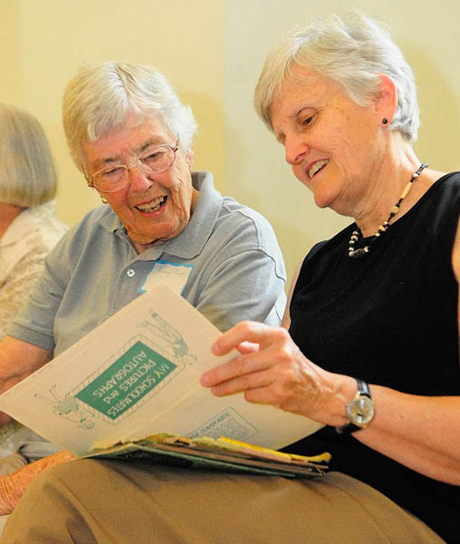 Audrey Fickett, left, looks at Melanie Lanctot's photo albums during a reunion for students of the town's one-room schoolhouses, on Friday at Asa Gile Hall in Readfield. Fickett, the mother of three of Lanctot's grade school classmates, worked in the cafeteria at the Readfield Elementary School that replaced the several smaller schools in the town.