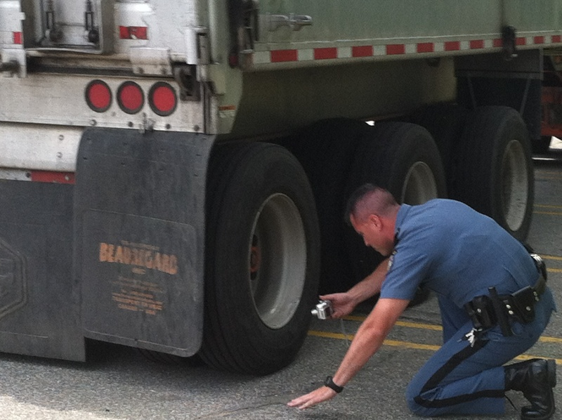 Maine State Police Trooper Joe Bureau inspects the rear tire of a Canadian truck police suspect was involved in Friday's fatal bicycle accident in Hanover.