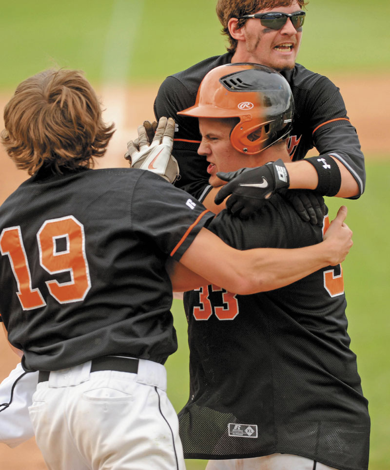 Winslow High School's Zach Guptill is mobbed by teammates after scoring the game-winning run in the Eastern Maine Class B regional final Thursday at Mansfield Stadium in Bangor. Winslow defeated Waterville 3-2 in 9 innings.