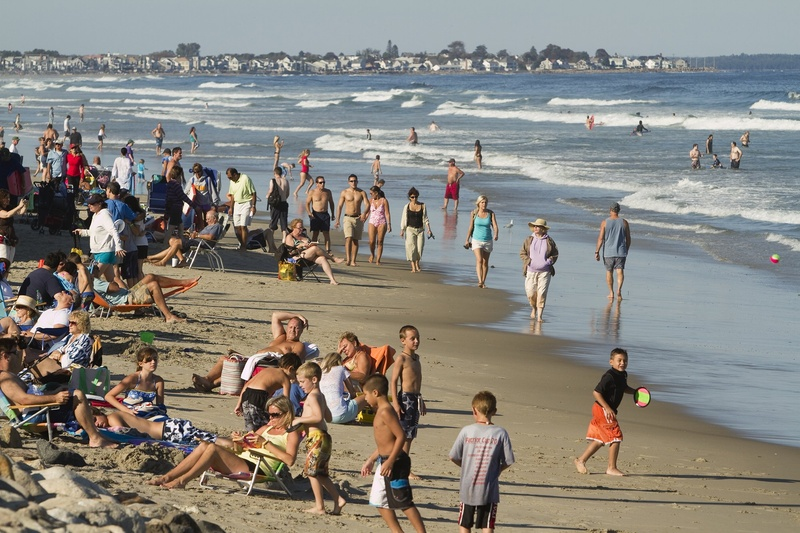Beachgoers congregate at Ogunquit Beach, one popular destination for tourists visiting Maine.