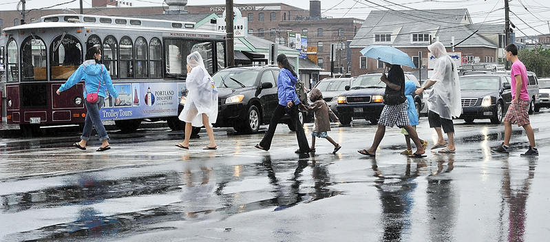 Tourists dressed in a variety of rain gear cross Commercial Street on Monday as rain falls at the beginning of the Fourth of July week.