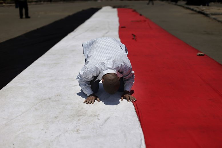 A supporter of ousted Egyptian President Mohammed Morsi prays on an Egyptian flag during the Friday prayer before a protest near the University of Cairo in Giza, Egypt.