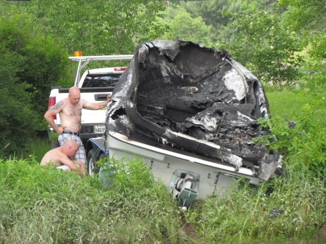 Two unidentified men trailer a boat that burned on the Kennebec River, in Pittston on Friday.