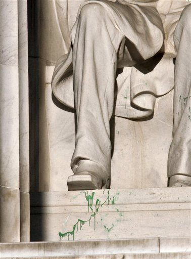 Splattered green paint is seen on the right shoe area of the Abraham Lincoln statue at the Lincoln Memorial in Washington. Police say the apparent vandalism was discovered early Friday morning. No words, letters or symbols were visible in the paint.
