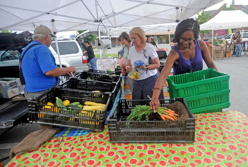 Noma Moyo, 21, a Colby College junior, picks up fresh carrots from 100 Acre Farm, at the Waterville Farmers' Market at the Concourse on Thursday.