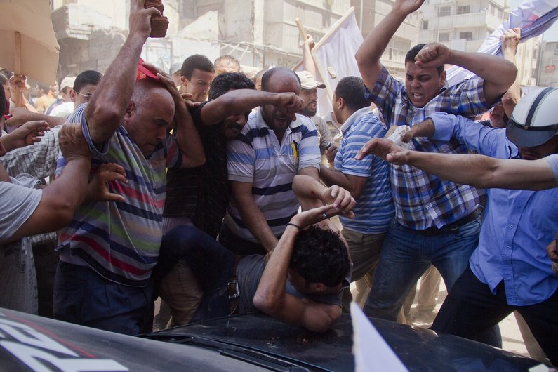 An Egyptian opposition protester is beaten by supporters of Egyptian president Mohammed Morsi, as a main raises a brick overhead, in downtown Damietta, Egypt, on Wednesday.