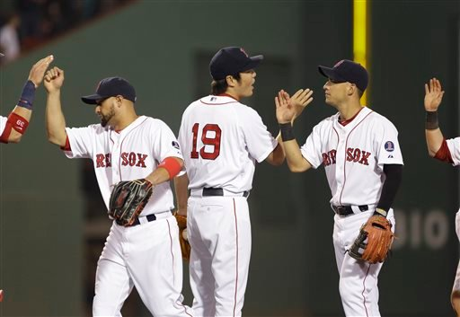 Boston Red Sox closer Koji Uehara (19) and teammates Shane Victorino, left, and Jose Iglesias, right, celebrate after they defeated the San Diego Padres 4-1 in an interleague baseball game at Fenway Park in Boston, Tuesday, July 2, 2013. (AP Photo/Elise Amendola)