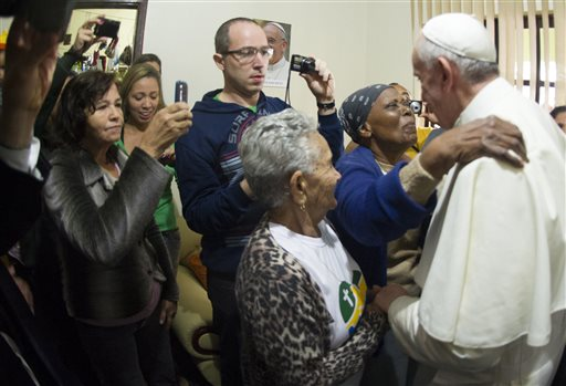 In this Thursday photo provided by the Vatican newspaper L'Osservatore Romano, Pope Francis meets with residents of the Varginha community in Rio de Janeiro. As a cardinal, Francis showed a special concern for the elderly that continues in his pontificate. But he's likely also aware of demographic trends in the church and society at large. The percentage of elderly is growing steadily around the globe, and caring for them is expected to become a major challenge.