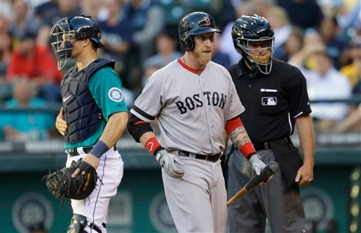Boston Red Sox' Mike Carp, center, walks to the dugout after being called out on strikes by home plate umpire Ed Hickox, right, in the fourth inning of a baseball game, Monday, July 8, 2013, in Seattle. Mariners catcher Mike Zunino is at left. (AP Photo/Ted S. Warren)