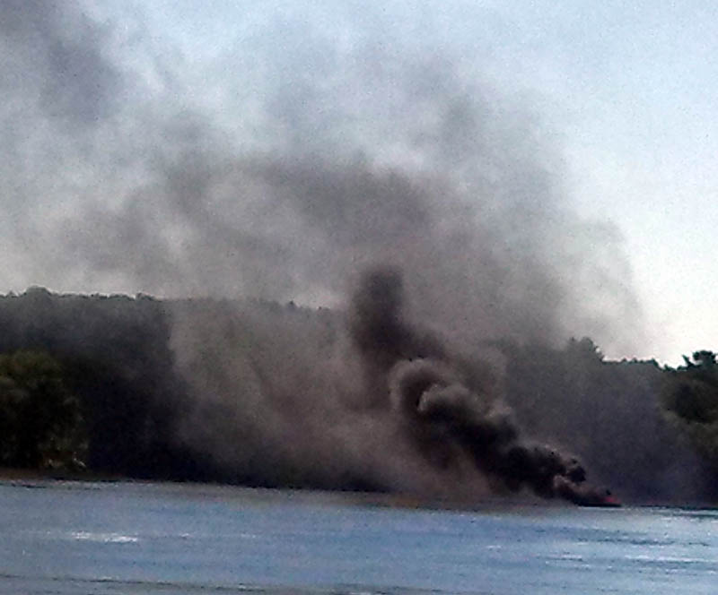 A burning motor boat drifts south on the Kennebec River, before running aground in Pittston on Friday.
