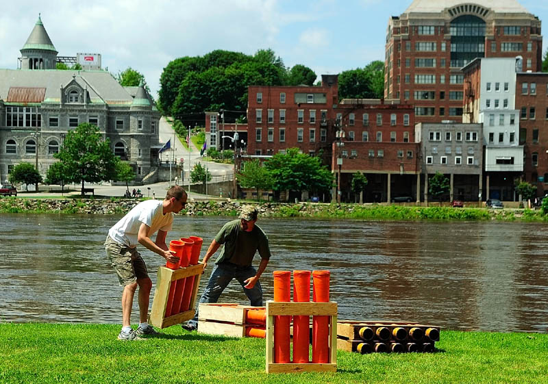 John Posey, left, and Chris Henderson stack fiberglass launch tubes on Thursday at the Eastside Boat Landing in Augusta. The crew from Central Maine Pyrotechnics started setting up for the 9:15 p.m. show around noon.