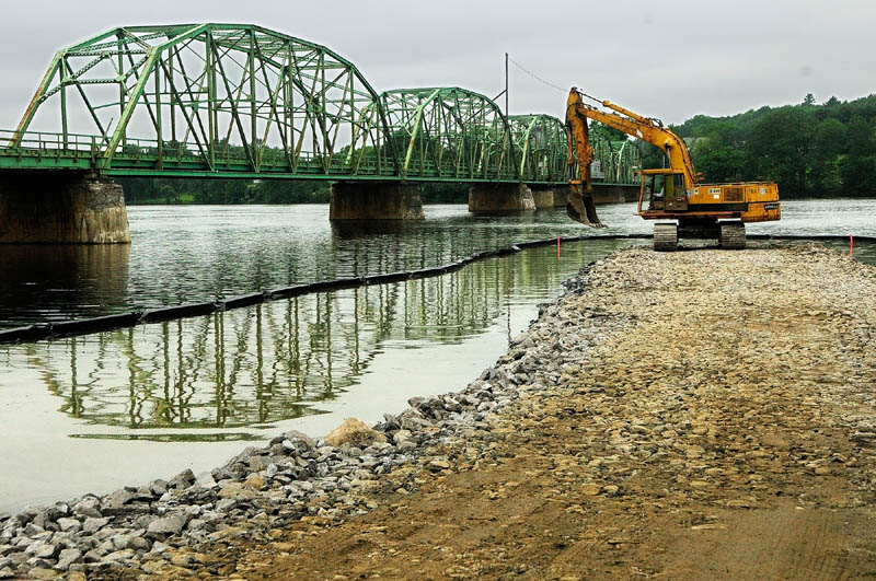 An excavator spreads a load of stone Wednesday as Reed & Reed Construction workers build a construction causeway for the work on the bridge over the Kennebec River to Richmond.