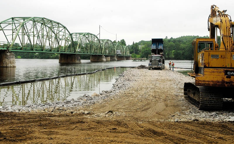 Construction crews work on a construction causeway on the Kennebec River Wednesday.