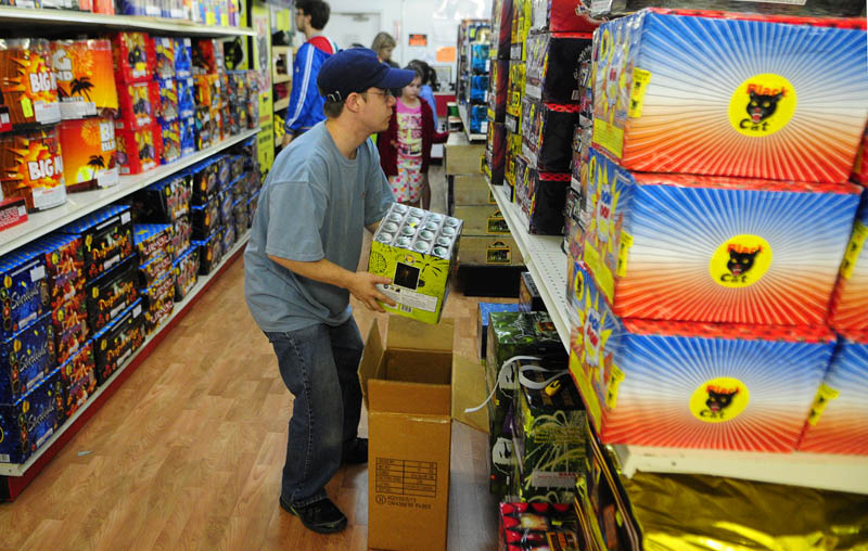 Brandon Pelletier restocks shelves on Tuesday at the Pyro City fireworks store on Route 202 in Manchester. Store manager Jeremy Mitchell said that they'd seen an increase in shoppers over the last two weeks.