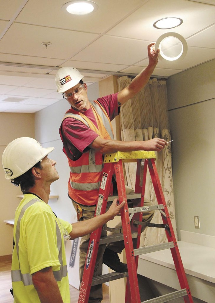 Steve Flanders, on ladder, works with his twin brother, Seth, while installing light fixtures inside Sebasticook Valley Hospital's new inpatient wing in Pittsfield on Wednesday. The brothers work for Elco Electric out of Bangor.
