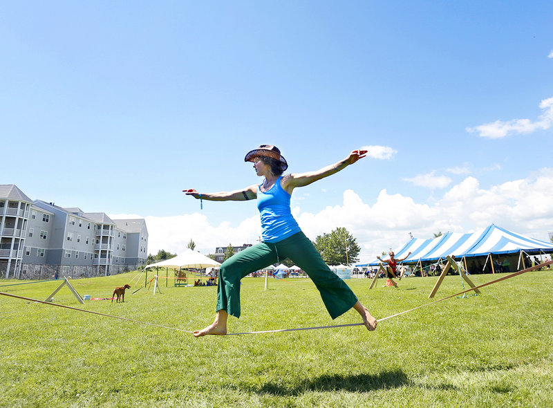 Instructor Meaghan Minogue performs a warrior II pose on a slack line during YogaFest at the East End Community School in Portland on Sunday.