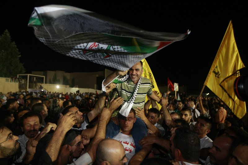 A released Palestinian prisoner, Esmat Mansour, center, waves a flag as he is cheered at the Palestinian Authority headquarters in the West Bank city of Ramallah on Wednesday. Israel released 26 Palestinian inmates, including many convicted in grisly killings, on the eve of long-stalled Mideast peace talks, angering families of those slain by the prisoners, who were welcomed as heroes in the West Bank and Gaza.