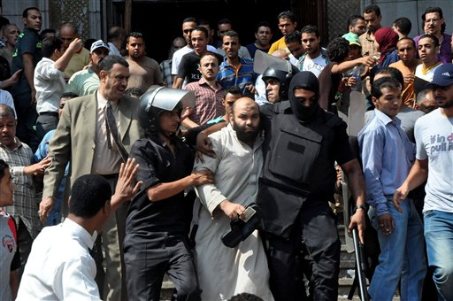 Egyptians security forces escort an Islamist supporter of the Muslim Brotherhood out of the al-Fatah mosque, after hundreds of Islamist protesters barricaded themselves inside the mosque overnight, following a day of fierce street battles that left scores of people dead, near Ramses Square in downtown Cairo, on Saturday. Authorities say police in Cairo are negotiating with people barricaded in a mosque and promising them safe passage if they leave.
