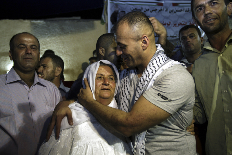 Burhan Sbeih, a released Palestinian prisoner, kisses his mother at his home in the West Bank village of Kofr Raei near Jenin city after his release Wednesday.