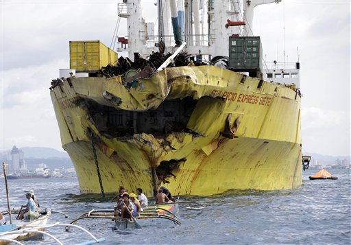 Volunteers search near the damaged cargo ship Sulpicio Express Siete a day after it collided with a passenger ferry off the waters of Talisay city, Cebu province in central Philippines, on Saturday.
