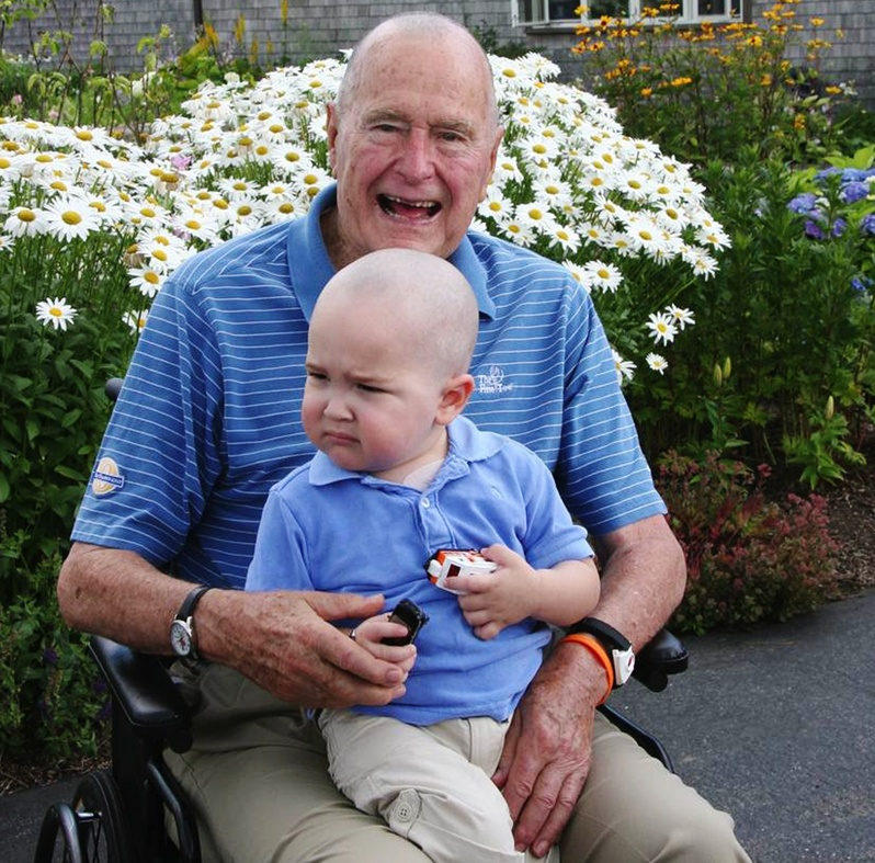 Former President George H. W. Bush sits with Patrick, 2, whose last name was withheld at the family's request, in Kennebunkport in this July 24, 2013, photo. Bush joined members of his Secret Service detail in shaving his head to show solidarity with Patrick, who is undergoing treatment for leukemia and is losing his hair as a result.