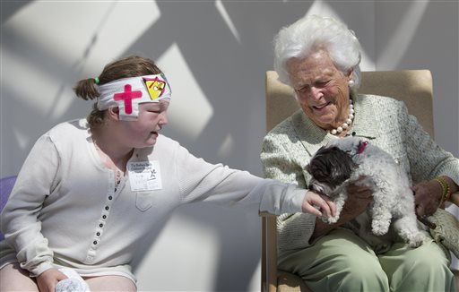 Kayla Veilleux, 14, left, of Oakland, gets a kiss from Tess, a maltipoo owned by former first lady Barbara Bush, at The Barbara Bush Children's Hospital at Maine Medical Center in Portland.